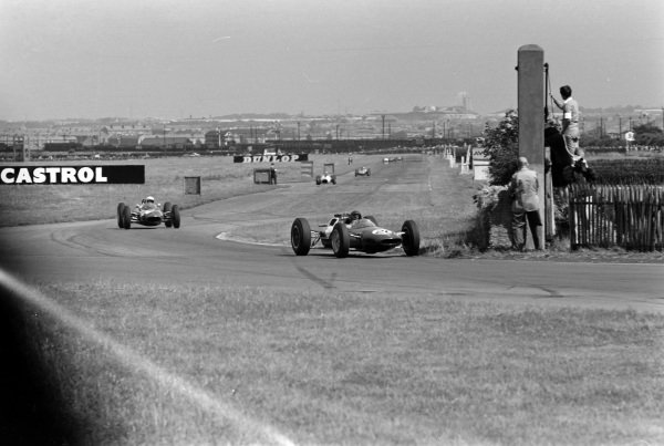 Jim Clark, Lotus 25 Climax, leads John Surtees, Lola 4 Climax.
